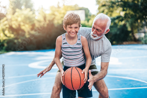 Obraz na plátně Grandfather and his grandson enjoying in beautiful sunny day and playing basketball