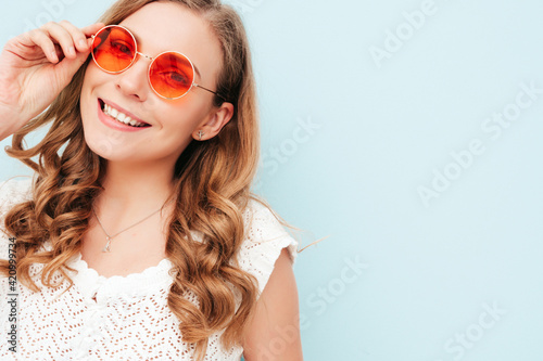 Young beautiful smiling female in trendy summer hipster suit clothes. Sexy carefree woman posing near light blue wall in studio. Positive model having fun indoors. Cheerful and happy in sunglasses