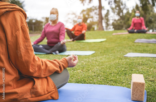 People doing yoga class outdoor sitting on grass while wearing safesty masks during coronavirus outbreak - Social distance and sport concept - Focus on teacher hand