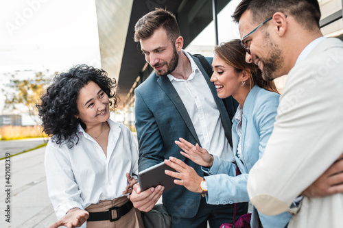 Coworkers standing outside in front of office buildings discuss about business plan.
