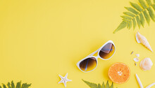 Summer Holiday And Vacation Concept, Including Beach Accessories Sunglasses, Starfish, Orange, Fern Leaves And Sea Shell On Yellow Background.