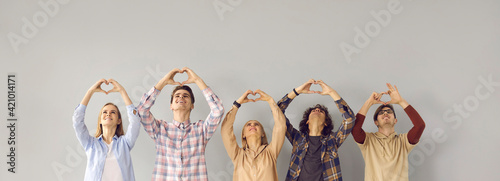 Fotografie, Obraz Group of happy grateful people looking up and doing symbolic heart shape hand sign gesture on gray background
