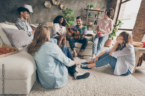 Fototapeta Portrait of attractive cheerful friends gathering playing guitar having fun pastime hobby holiday in house loft brick style interior indoors obraz