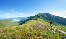 A Female Hiker Walking, Hiking Along A Mountain Path Towards The Summit Of Ben Lawers From The Top Of Beinn Ghlas In The Scottish Highlands, UK Landscape.