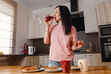Dark-haired Thirty-year-old Woman Drinks Wine From Large Glass At Home In The Kitchen