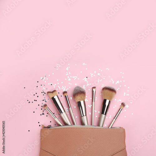 Different makeup brushes, case and shiny confetti on pink background, flat lay Fototapet
