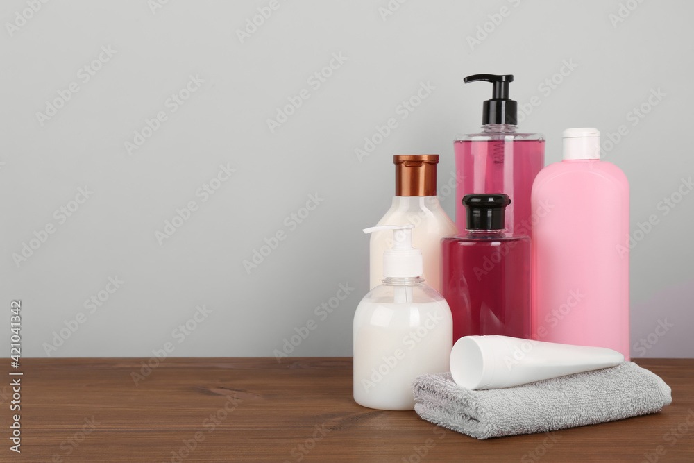 Different shower gel bottles with towel on wooden table. Space for text - obrazy, fototapety, plakaty