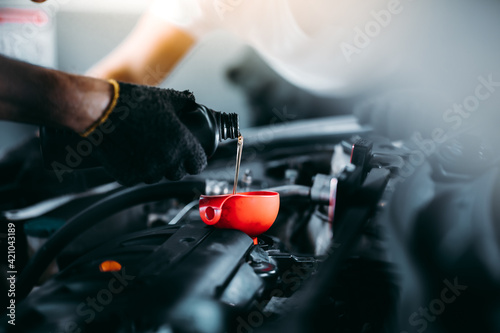 Pouring oil to car engine. Closue up male mechanic hand working and service in Car Service station