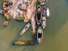 Aerial View Of Ships Wrecks Docked Along A Small Shipyard Harbour Facing Corroios Lagoon In Setubal, Portugal.