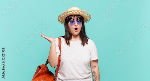 young traveler woman looking surprised and shocked, with jaw dropped holding an object with an open hand on the side