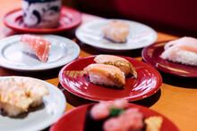 Sushi And Sashimi. Dishes Of Sushi And Sashimi Rolling On Conveyer Belt.