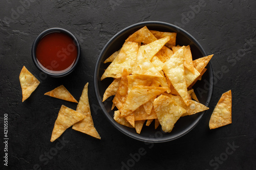 Fototapeta Corn chips or nachos chips in a bowl with tomato sauce on the side on a black rustic background, top view. obraz