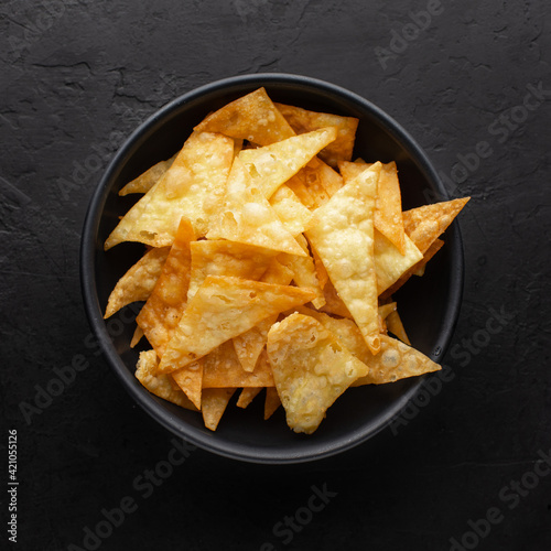 Fototapeta Corn chips or nachos chips in black bowl on black rustic background, top view. obraz