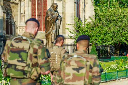 PARIS, FRANCE - JULY 1, 2017: Pope John Paul II statue guarding soldiers of National Armed Forces in Notre Dame of Paris, keeping security after recent terrorist attacks in Paris Wallpaper Mural