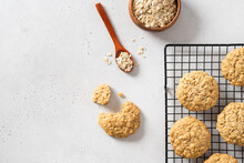 Homemade Oatmeal Cookies With Banana, Oats And Nuts On A Grid And Oats Flakes On White Background, Top View, Copy Space. Healthy Food. Oatmeat Biscuits Recipe