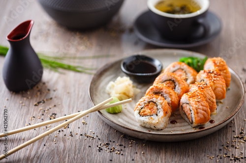 Fototapeta Baked sushi maki rolls with salmon, crab and spicy sauce on a plate with chopsticks, soy sauce, wasabi and ginger. Japanese traditional fish food closeup served for lunch in modern gourmet restaurant obraz