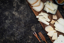 The Variety Of Hard Cheeses On A Wood Cutting Board With Wooden Cutlery. Tasty Cheese Starter. Culinary Cheese Background. Food For Wine And Romantic, Cheese Delicacies, Brie, Camembert And Parmesan.