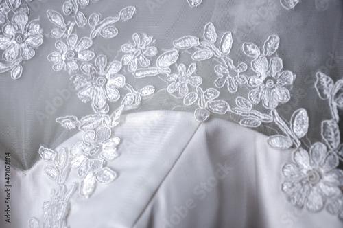 Photo Detailansicht eines Brautkleides.  Bestickt mit floraler Spitze