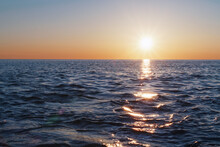 The Setting Sun Goes Into The Sea On The Horizon With A Light Track And Reflections On The Sea.