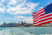 San Francisco, California, United States - August 14, 2016: American Flag In San Francisco Bay Cityscape. Tour To Alcatraz Island By Ferry Boat Waving In San Francisco Pier With Cityscape. Cloudy Sky.