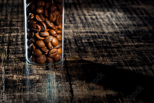 Fototapeta Coffee beans close up. Coffee in a glass jar on a wooden board. Coffee texture on a black shabby table. Contrasting dramatic light as an artistic effect. obraz