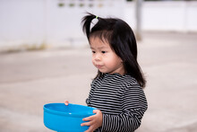 Little Asian Child Holding Blue Bowl. Black Haired Girl Was Helping With Housework By Using Water Dipper In Front Of The House. Child Wear Black Long-sleeved Striped Shirt. Children 3-4 Years Old.