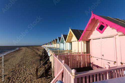 Платно Parade of colourful beach huts on Mersea Island in Essex