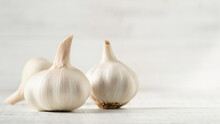 Three Garlic Bulbs On A White Background.