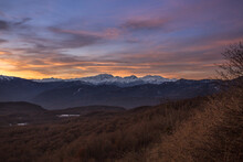 Morning Landscape In The Mountains Of Adygea. View Of The Valley And Snowy Peaks Against A Background Of Blue Sky And Pink Clouds. The Sun Rises Behind The Caucasus Mountains