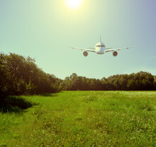 Passenger Plane Over The Field And Forest. A Bright Yellow Sun Shines In The Sky