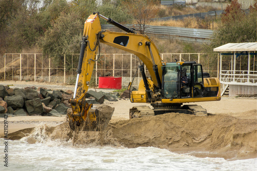 Obraz na plátně Excavator digs sand on the beach of the Bulgarian sea coast
