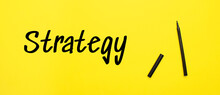 Strategy Word And A Pen Marker On Yellow Background. Business Concept.