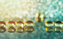 Macro Photo Of A Row Of Fish Oil Capsules On Glass With Bokeh And Glare, One Capsule Is Knocked Out Of The Row. Turquoise Yellow Bokeh.