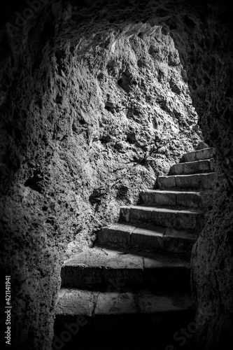 Stone steps of ancient staircase carved in the rock, black and white image, concepts of entrance or exit Fototapeta