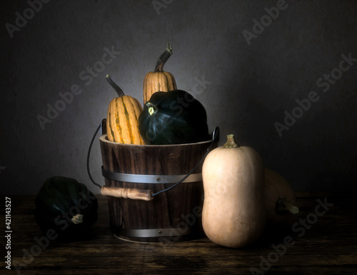 Fototapeta Three types of winter squash, Delicata Squash, acorn squash and butternut squash and a bucket, viewed from the side, on wooden table, whole fruit, still life display obraz