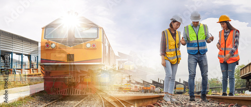 Fotografie, Obraz A group of rail transport specialist engineers is working on the train tracks