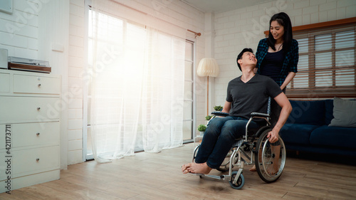An asian man in a wheelchair in the home after a car accident and his wife to give encouragement. The concept of Mutual care and new technology has made people with disabilities Equality in society.
