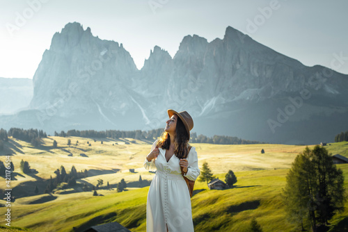 Happy young girl with white dress, hat and backpack in Alpe di Siusi, Dolomites.