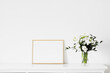 Golden horizontal frame and bouquet of fresh flowers on white furniture, luxury home decor and design for mockup creations