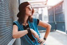 A Young Stylish Hipster Girl In A Daring Image In A Cap And Sunglasses Poses In The City In The Rays Of The Sunset On An Urban Background. Fashion, Style, Retro, Sass, Teen