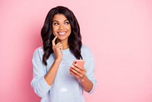 Photo Of Curious Lady Hold Cellphone Finger Cheek Look Side Empty Space Wear Blue Sweater Isolated Pink Background