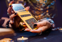 Esotiricism. The Witch Shuffles The Tarot Cards In Her Hands. Close-up. The Concept Of Witchcraft And Divination