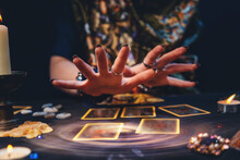 Astrology. The Sorceress Conjures Over The Tarot Cards Spread Out On The Table. Hands Close-up. The Concept Of Magic And Esotericism