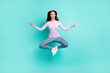 Full length body size view of attractive dreamy girl jumping sitting lotus pose meditating isolated over turquoise bright color background