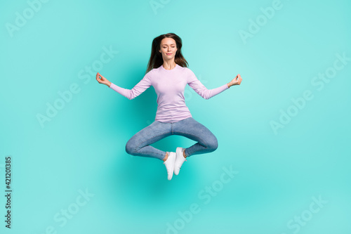 Fototapeta Full length body size view of attractive dreamy girl jumping sitting lotus pose meditating isolated over turquoise bright color background obraz