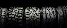 Off-road Tires And Tires For Crossovers And SUVs Stand In A Row On A Black Background