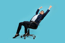 Young Businessman Stretching In Comfortable Office Chair On Turquoise Background
