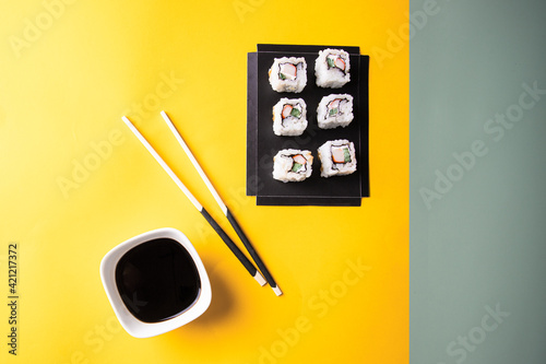 Fototapeta Top view of sushi and rolls set n black try and soy sauce with chopsticks on bright yellow green background. Japanese food concept. obraz