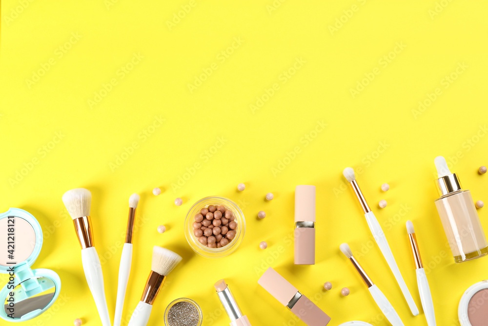 Fototapeta Flat lay composition with makeup brushes on yellow background, space for text
