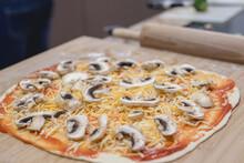 Detalle De Una Pizza Vegana En Una Encimera De Cocina De Madera. Base De Pizza Con Queso Y Champiñones.